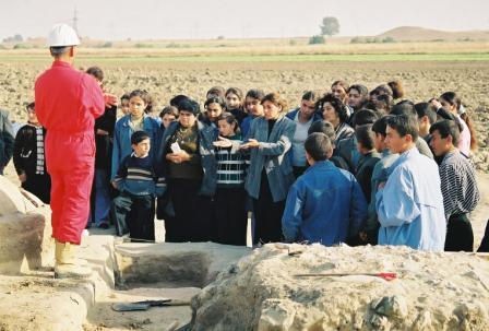 Safar Explaining Borsunlu Bronze Age Kurgan to a school party from the the local village
